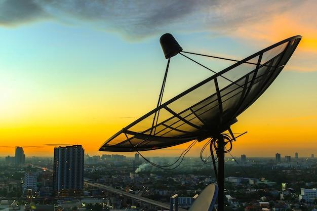 Cielo de la antena parabólica en el crepúsculo de la ciudad