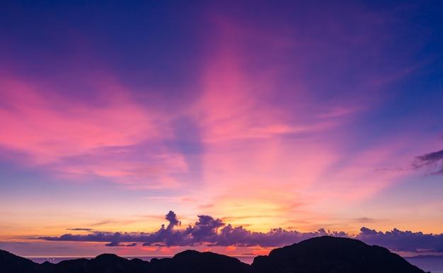 El cielo azul hermoso del paisaje crepuscular y la luz de pandora con primero plano de la silueta de la montaña en el mar en tailandia