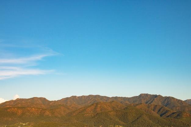 Cielo azul y montaña con espacio de texto libre.