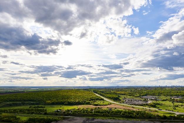 Cielo azul con nubes sobre árboles verdes y caminos fuera de la ciudad.