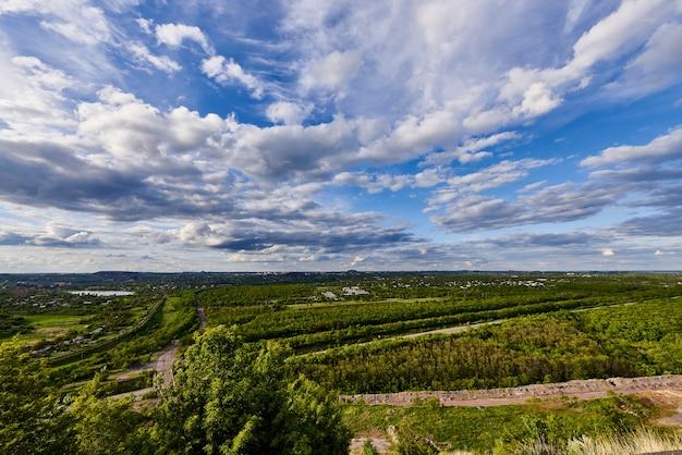 Cielo azul con nubes sobre los árboles verdes fuera de la ciudad en la luz del sol.