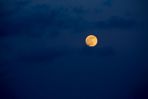 Cielo azul oscuro con luna llena y nubes.