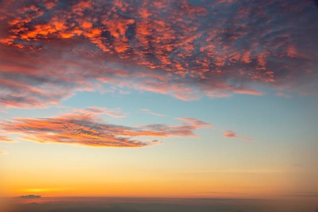 Cielo azul del sol naciente con la nube anaranjada por la mañana