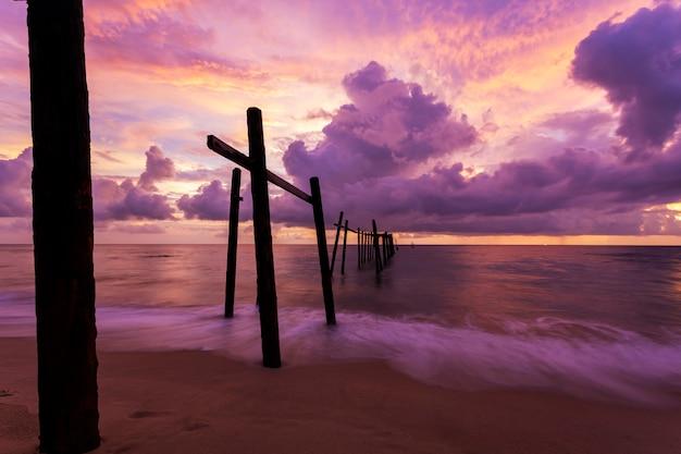 Cielo dramático de la puesta del sol hermosa sobre el mar con el puente de madera viejo en khao pilai en phang- nga tailandia