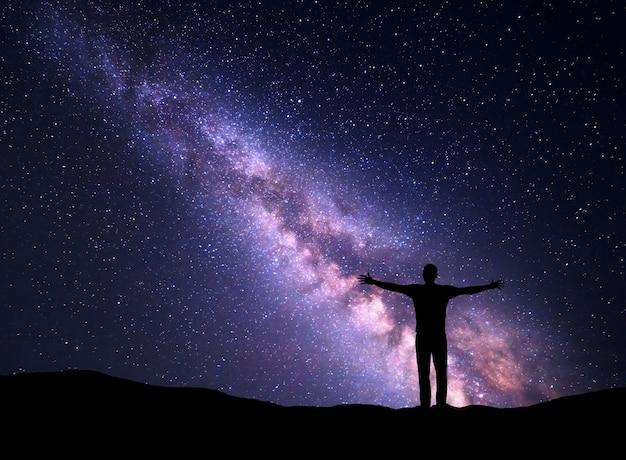Cielo nocturno con la vía láctea y la silueta de un hombre