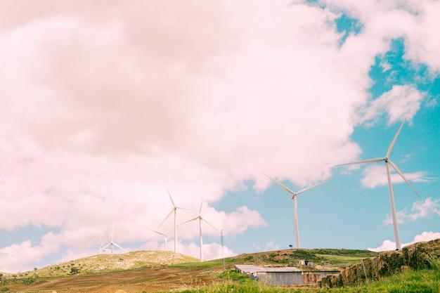 Cielo nublado sobre lo rural con molinos de viento.