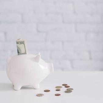 Cien billetes de dólar en la ranura de piggybank con monedas en el escritorio