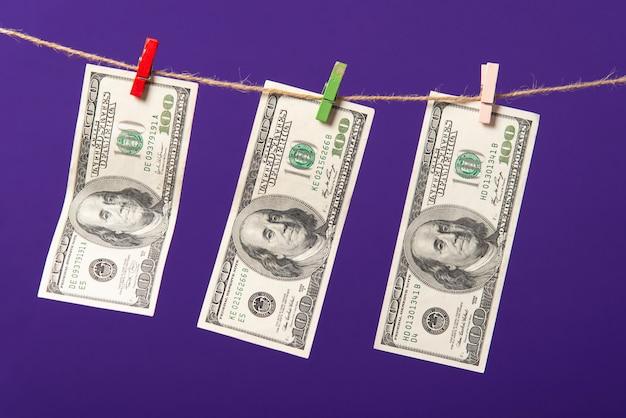 Cien dólares colgando en el tendedero con clips de madera sobre fondo azul.
