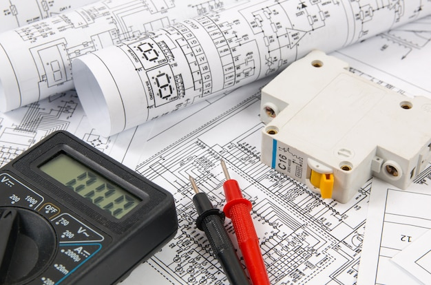 Ciencia, tecnología y electrónica. impresión de planos de ingeniería eléctrica con disyuntor y mulyimeter. desarrollo científico.