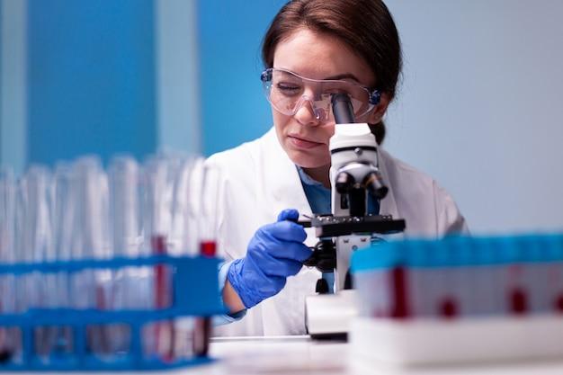 Científica en bata blanca mirando en microscopio de gama alta para experiencia en farmacia