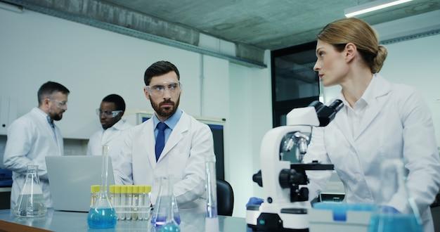 Científica caucásica en la túnica blanca mirando en el microscopio mientras investiga y su colega masculino prueba un poco de líquido en tubo en la computadora portátil
