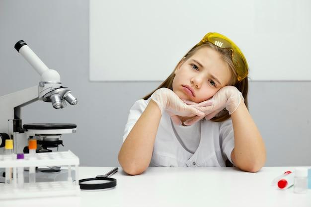 Científica chica con gafas de seguridad y microscopio en el laboratorio