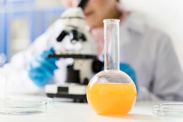 Científica desenfocada con microscopio y cristalería de laboratorio