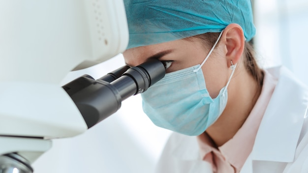 Científica femenina mirando cuidadosamente a través de un microscopio.