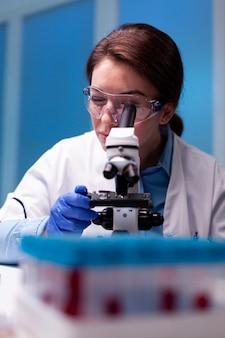 Científico ajustando farmacia microscop en laboratorio, experimento, experiencia, pruebas de vacunas