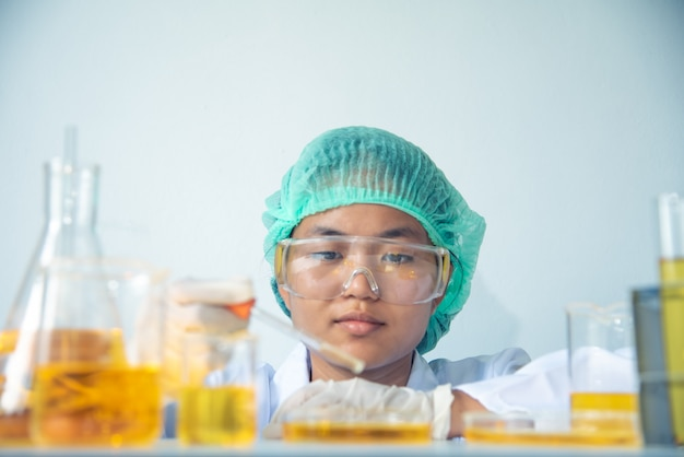Científico asiático joven de la muchacha con el amarillo del tubo de ensayo que hace la investigación en laboratorio.