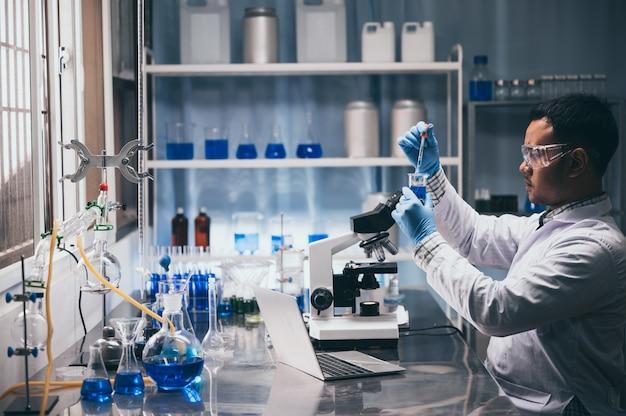 Científico asiático sostiene un tubo de ensayo lleno de líquido en el laboratorio.
