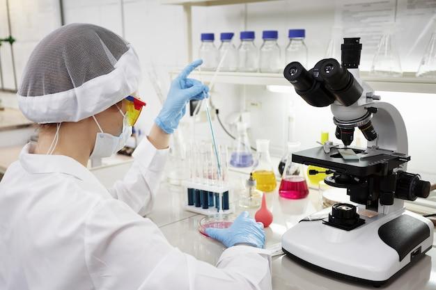 Científico atractivo joven estudiante de doctorado observando el cambio de color del indicador azul en el tubo de vidrio