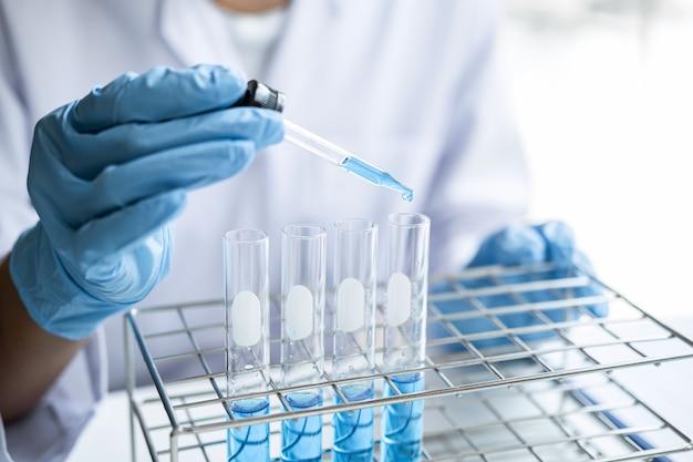 Científico en bata de laboratorio con tubo de ensayo con gota de líquido de color sobre equipo de vidrio