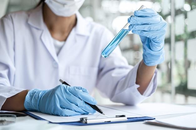 Científico en bata de laboratorio con tubo de ensayo con reactivo