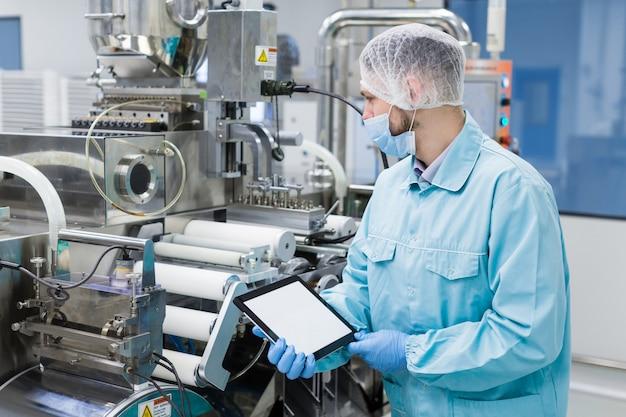 Científico cerca de la máquina de acero sostener tableta vacía