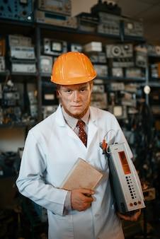 Científico extraño en un casco sosteniendo un libro y un dispositivo electrónico, ingeniero en laboratorio. equipo de laboratorio, taller de ingeniería
