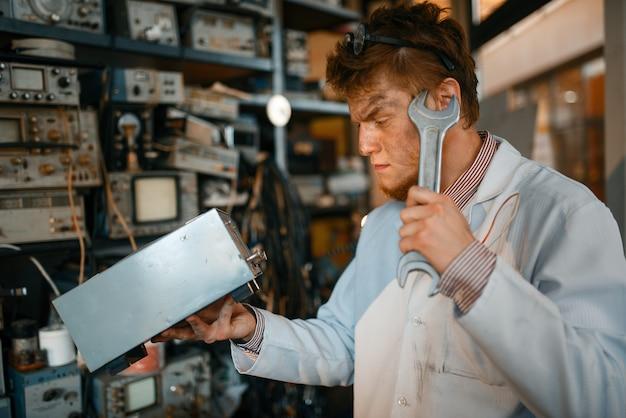 Científico extraño con dispositivo eléctrico y llave enorme, prueba en laboratorio. equipo de laboratorio, taller de ingeniería