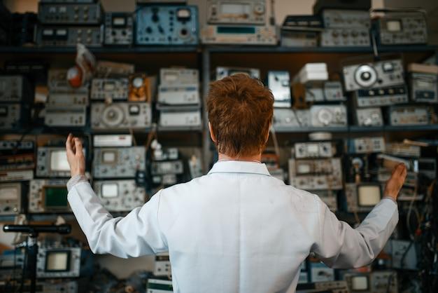 Científico extraño en estante con dispositivos electrónicos en laboratorio, vista posterior. equipo de laboratorio, taller de ingeniería