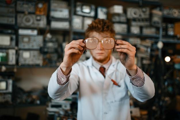 Científico extraño mira a través de las gafas en el laboratorio. equipo de laboratorio, taller de ingeniería