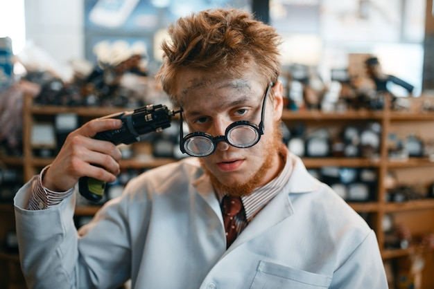 Científico extraño sostiene un destornillador en su sien, prueba peligrosa en laboratorio. equipo de laboratorio, taller de ingeniería