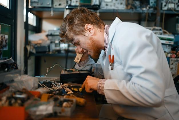 Científico extraño trabaja con soldador, prueba en laboratorio. equipo de laboratorio, taller de ingeniería