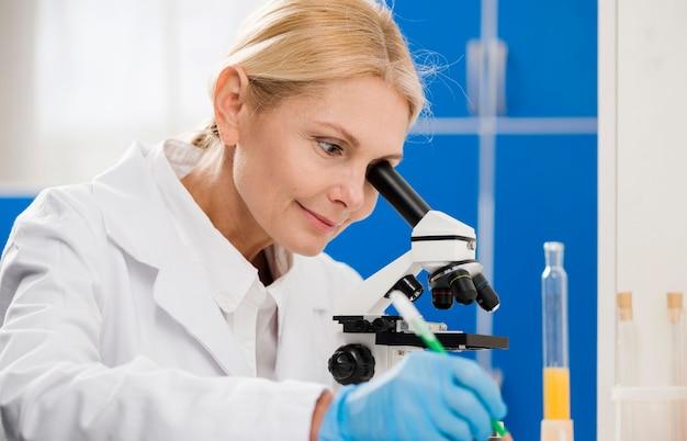 Científico femenino analizando con microscopio en el laboratorio
