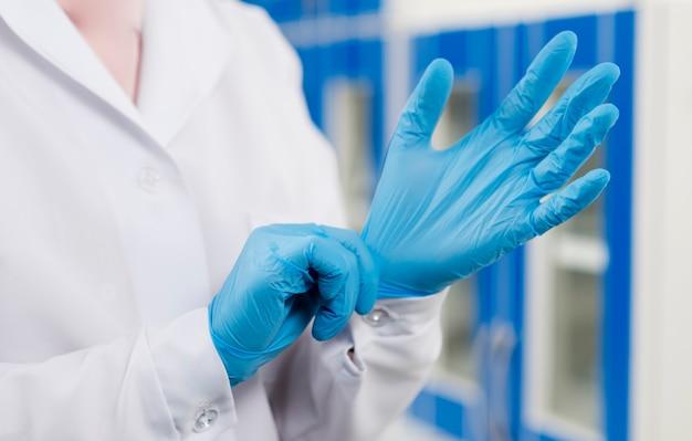 Científico femenino poniéndose guantes quirúrgicos