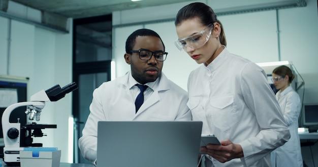 Científico joven afroamericano en la túnica blanca y gafas trabajando en la computadora portátil y el microscopio durante la investigación, mientras que su compañera caucásica viene con una tableta