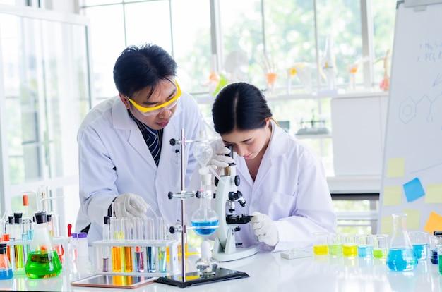 Científico joven que mira a través de un microscopio en un laboratorio. joven científico investigando.