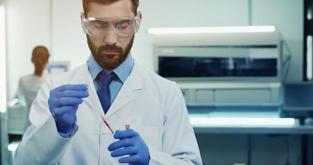 Científico de laboratorio caucásico joven en gafas haciendo un análisis de sangre con un tubo en las manos. retrato. de cerca