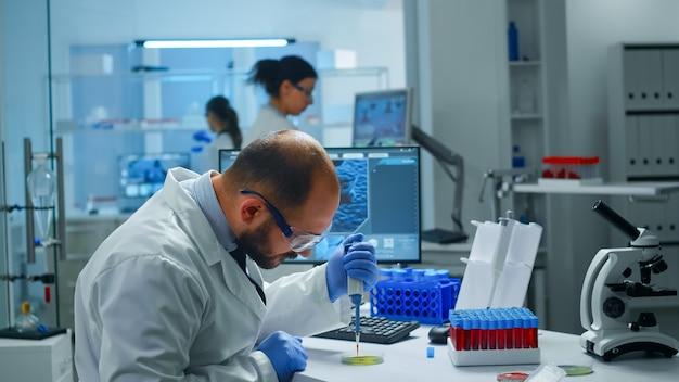 Científico en el laboratorio médico que examina el descubrimiento de fármacos poniendo una muestra de sangre en una placa de petri con una micropipeta