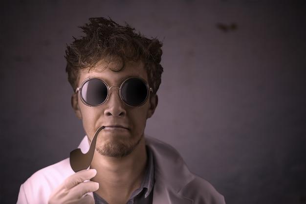 Científico loco con una pipa que fuma en un abrigo y gafas de sol en un fondo oscuro viejo de la pared