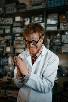 Científico loco en vasos realiza una prueba en laboratorio. equipo de laboratorio, taller de ingeniería