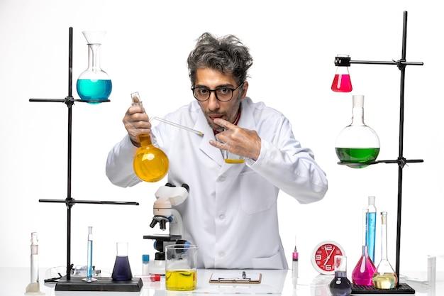 Científico masculino de vista frontal en traje médico trabajando con diferentes soluciones