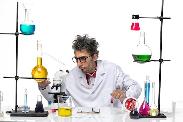 Científico masculino de vista frontal en traje médico trabajando con matraces y soluciones