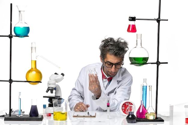 Científico masculino de vista frontal en traje médico trabajando con matraz