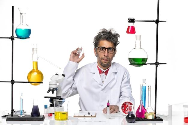 Científico masculino de vista frontal en traje médico trabajando con soluciones