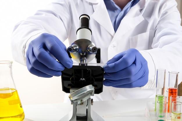 El científico mira a través de un microscopio. el doctor hace las pruebas en el laboratorio.