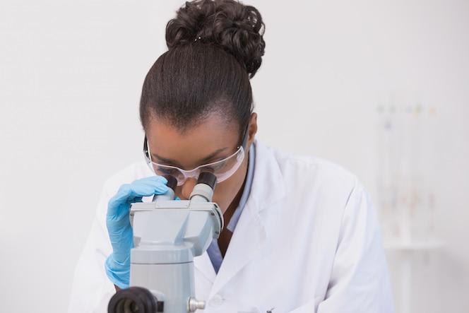 Científico mirando a través de un microscopio