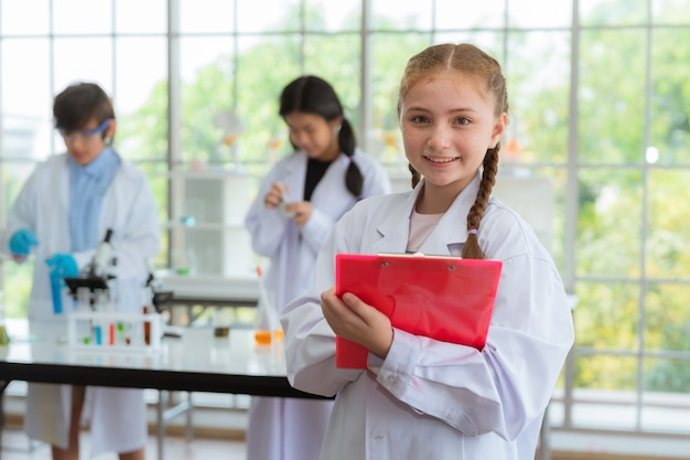 Científico de la muchacha que sonríe en sitio del laboratorio en escuela concepto de la ciencia y de la educación.