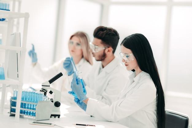 Científico de la mujer mirando el tubo con líquido