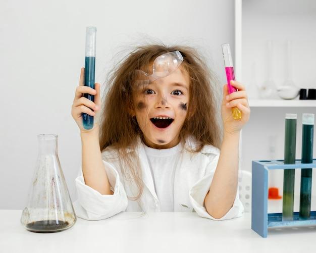 Científico de niña sonriente en el laboratorio con tubos de ensayo y experimento fallido