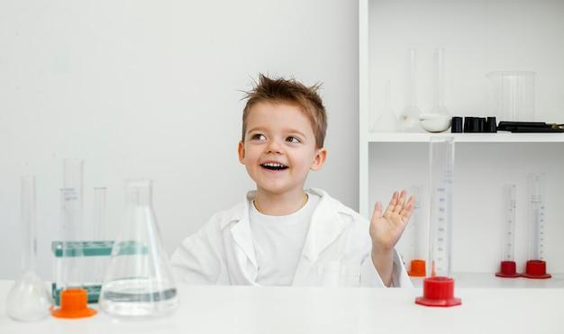 Científico de niño feliz en el laboratorio con tubos de ensayo