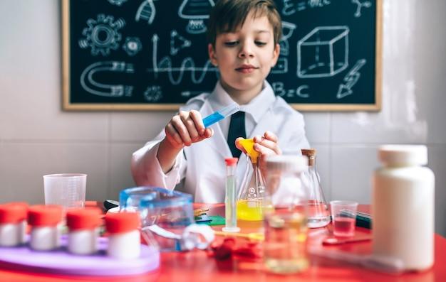 Científico de niño pequeño jugando con líquidos químicos contra de pizarra con dibujos. enfoque selectivo en las manos.